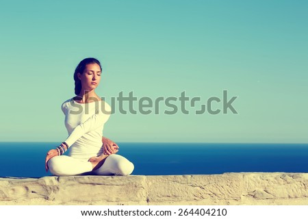 Stock Photo Front portrait of gorgeous young woman practicing yoga on a sunny day with amazing sea horizon on background, woman seeking enlightenment through meditation,relaxed girl performing yoga routine,filter