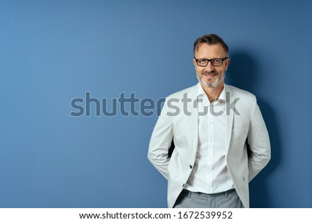Front portrait of handsome middle-aged man in white shirt, blazer and glasses, leaning back on the wall with his hands behind his back, standing against blue background with copy space