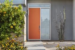 Front reddish orange door, exterior view of a mid-century house