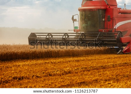 Front shot of a harvester working in the field #1126213787