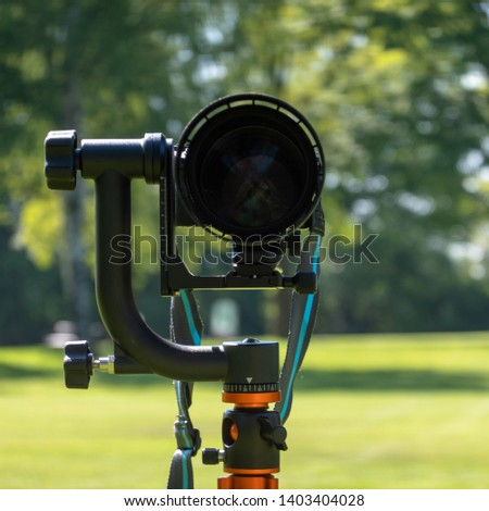 Front shot of a large telephoto lens mounted outdoors on a tripod with manual heavy gimbal, intentionally blurred background #1403404028