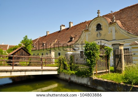 front side of an old yellow manor with a bridge - stock photo