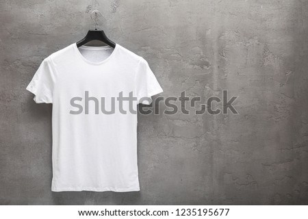 Front side of male white cotton t-shirt on a hanger and a concrete wall in the background. T-shirt without print and copyspace for your text on right side Foto stock ©