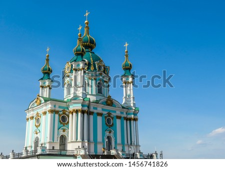 Front side of the St Andrew's Church, Kiev, Ukraine. The church is small and painted blue and white, with many decorations on it's facade. Picture taken from under the church. Clear and blue sky