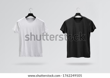Front sides of male black and white cotton t-shirts on a hanger isolated on white background. T-shirts without print Foto stock ©