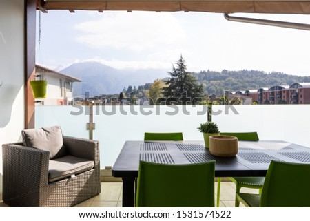 Front terrace view with furniture. Table, chairs and potrona. View of the Swiss hills in Ticino. Nobody inside