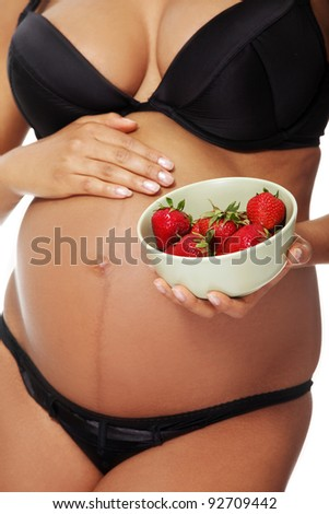 Front vierw belly closeup of a young beautiful pregnant woman holding w salad-bowl with strawberries in front of her tummy, over a white background.