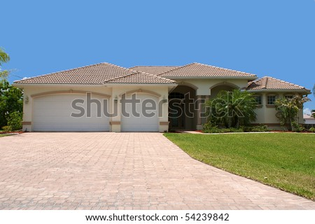 front view a generic florida home sits on a small grass covered hill with garage, palm trees and a clear blue sky, looking up the driveway.