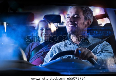 front view. A handsome man driving his car at night in the rain.  At the back his little daughter smiles to her dad in the mirror