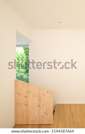 Front view and entrance detail with raw wood parapet and parquet. White walls.  Nobody inside