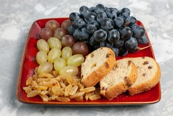 front view cake slices with grapes and raisins inside red plate on white background cake biscuit sugar sweet pie fruit