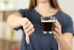 Front view close up of a woman hands holding a coffee cup with thumbs down at home