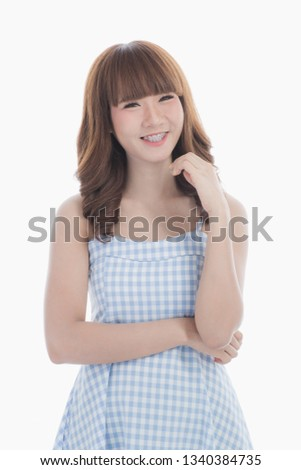 Front view close-up portrait of young beautiful Asian woman with curly long dark brown hair in light blue checked dress stand up straight  isolated white background
