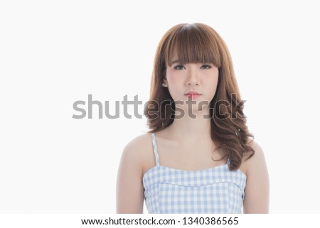 Front view close-up portrait of young beautiful Asian woman with curly long dark brown hair in light blue checked dress stand up straight and looking at camera on isolated white background