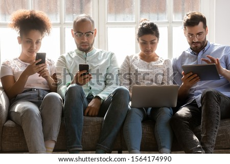 Front view concentrated young diverse people sitting together on sofa, using different gadgets. Addicted to technology mixed race students, spending time with electronic devices, ignoring each other. stock photo