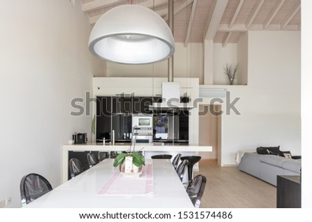 Front view dining room with white table, black chairs and modern kitchen. Nobody inside