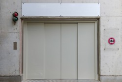 Front view, Entrance to concrete wall  of underground car garage in front of closing Elevator Lift with caution of limited 1.95 m car's height.