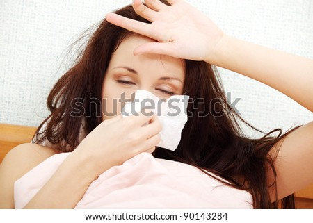 Front view face closeup of a beautiful young woman lying in bed, having a cold, sneezing in a tissue and resting her hand on the forehead.