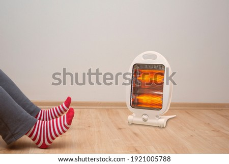 Front view, female feet standing on parquet floor, in front of halogen heater Stock photo ©