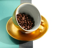 Front view for golden porcelain coffee cup copy with fresh roasted arabica beans. Large golden cup in antigravity position on the geometric grey and tiffany blue background.