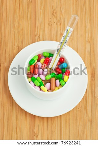 front view from cup with multicolored tablets and capsules and thermometer