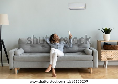 Photo of  Front view full length joyful young mixed race woman relaxing on cozy couch in living room, holding remote controller, turning on cooler system air conditioner, setting comfortable temperature.