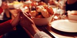 Front view mid section of a group of young adult multi-ethnic male and female friends sitting around a table holding hands saying grace before eating Thanksgiving dinner at home together