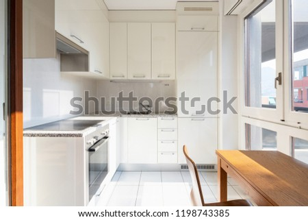 Front view modern kitchen with wooden table and window. Nobody inside