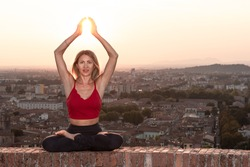 Front view of a back light of a faithful woman in yoga position holding the sun at sunset or sunrise in a beautiful city location with a warm background