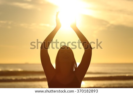 Front view of a back light of faithful woman silhouette holding sun on the beach at sunrise with a warm background