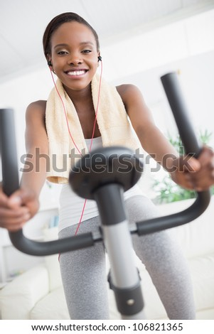 Front view of a black woman doing exercise bike in a living room
