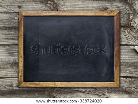 Front view of a blank blackboard over a weathered wooden surface Foto stock ©
