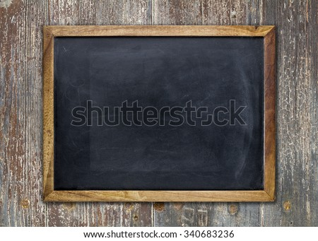 Front view of a blank blackboard over a weathered wooden surface
