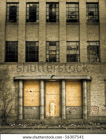 Front view of a boarded-up abandoned building from the street in Detroit, Michigan.