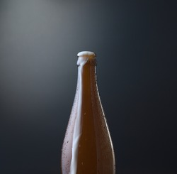 Front view of a bottle of cold beer with overflowing foam against dark blue grunge background. Cold alcoholic beverage, international beer day concept. Organic photography style.