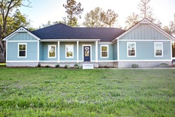 Front view of a brand new construction house with blue vinyl siding, a  ranch style home with a yard