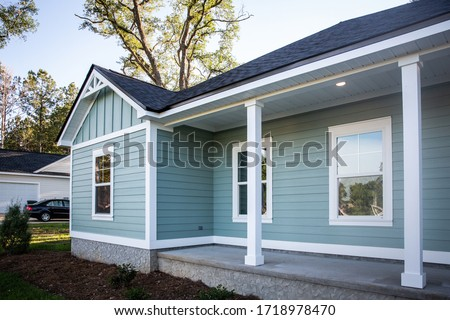 Front view of a brand new construction house with blue vinyl siding, a  ranch style home with a yard Foto stock ©