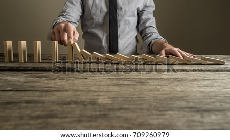 Front view of a businessman stopping domino effect with his finger. Security and insurance concept. #709260979