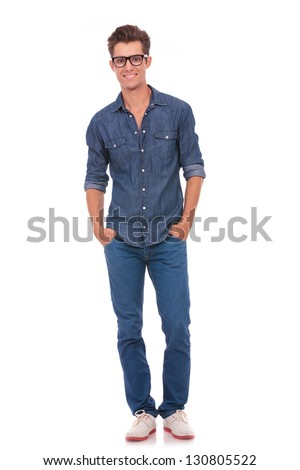 front view of a casual young man standing with his hands in his pockets and smiling to the camera. isolated on a white background
