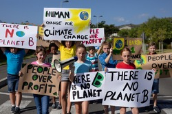 Front view of a diverse group of elementary school pupils walking down a road in the sun on a protest march, carrying signs with environmental and conservation slogans on them, one girl holding a