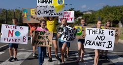 Front view of a diverse group of elementary school pupils walking down a road in the sun on a protest march, carrying signs with environmental and conservation slogans on them, one girl shouting in a