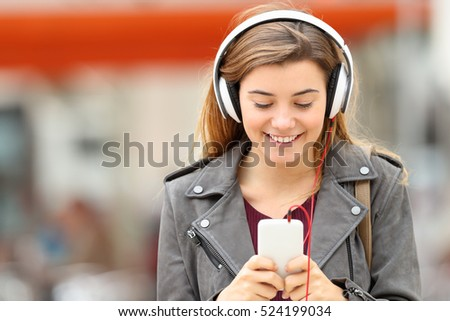 Shutterstock Front view of a fashion girl listening music with headphones and smart phone on line and walking towards camera in the street