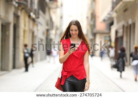 Front view of a fashion happy woman walking and using a smart phone on a city street #274705724