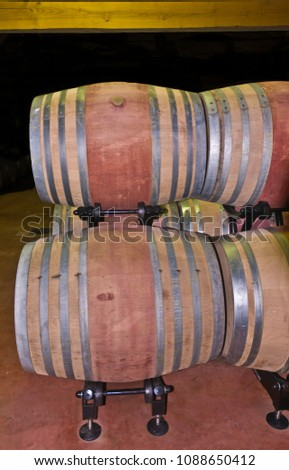 Front view of a french Bordeaux chateau's wine cellar with new oak wood wine barrels for storage, of newly harvested 2013 grapes #1088650412