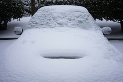 Front view of a frozen sports car on the streets after a winter storm of snow and freezing rain.