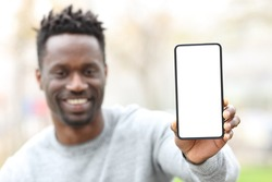 Front view of a happy black man showing phone screen mockup in a park
