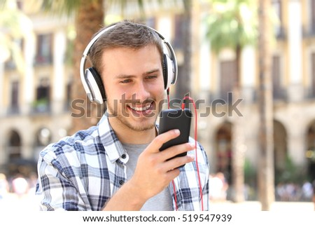 Front view of a happy guy with headphones listening music on line and watching media in a smartphone in the street