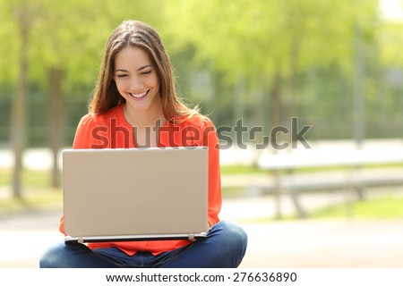 Front view of a happy student girl working with a laptop in a green park of an university campus