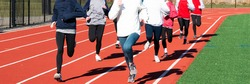 Front view of a large group of high school girls running together in lanes on a red track.