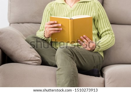 Front view of a legs of a man reading a book sitting on a sofa in the living room in a house interior in winter